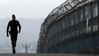 Muro fronterizo vigilado por un policía