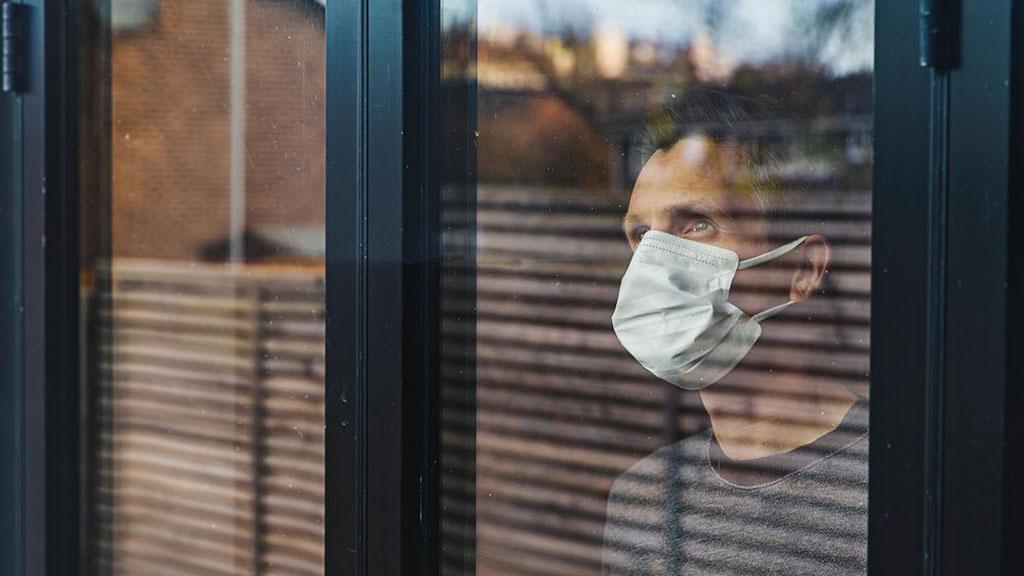 Hombre con mascarilla mirando el exterior a través de una ventana